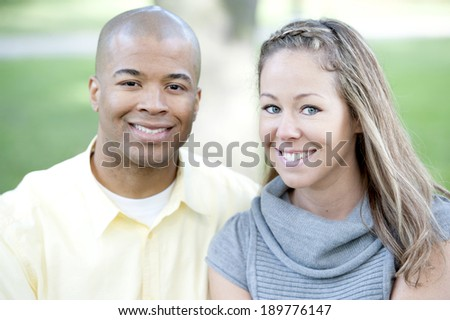 Happy young interracial couple posing together on a sunny day. - stock photo