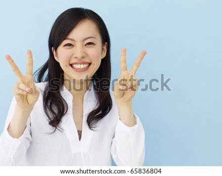 Happy young japanese girl showing victory sign isolated on blue background - stock photo