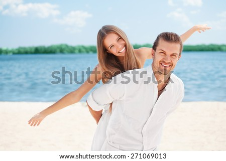 Happy young joyful couple having beach fun piggybacking laughing together during summer holidays vacation on the beach. Beautiful energetic fresh couple, man and woman - stock photo