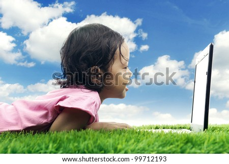 Happy young kid looking at computer laptop. Shot in meadow - stock photo
