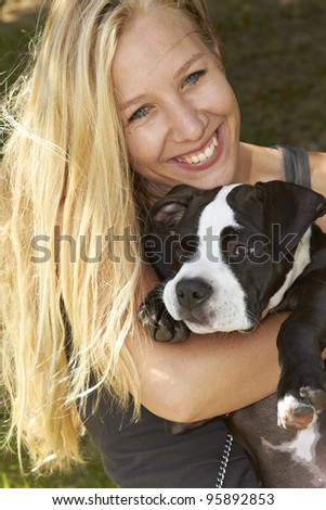 Happy young lady embracing her Pit Bull puppy - stock photo