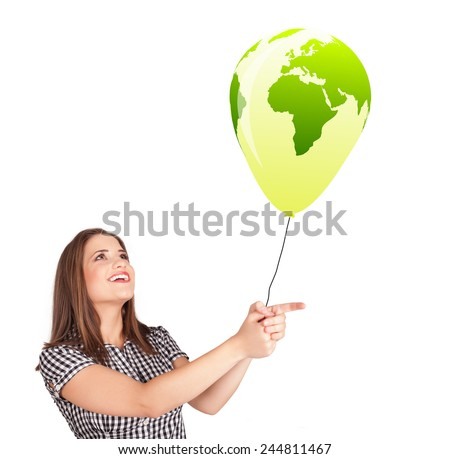 Happy young lady holding a green globe balloon - stock photo