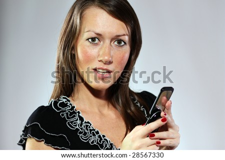 Happy young lady lying talking on mobile phone - stock photo