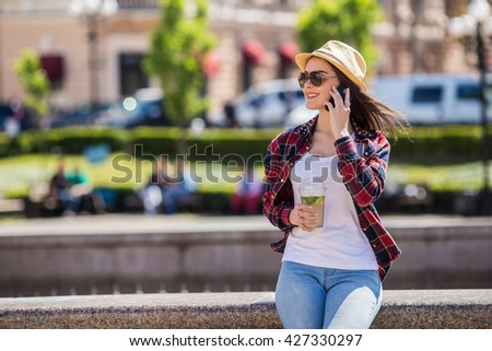 Happy young lady talking on mobile phone on the street - stock photo
