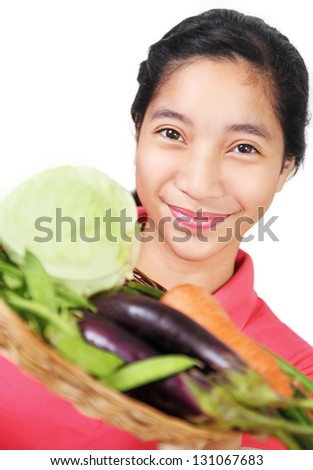 Happy young lady with a tray of fresh vegetables. - stock photo