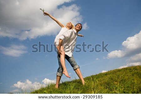 Happy Young love Couple - jumping under blue sky - stock photo