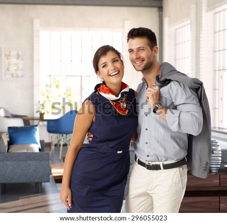 Happy young loving couple embracing at home before leaving. - stock photo