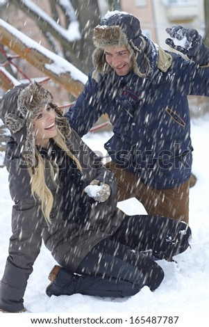 Happy young loving couple having fun at winter in snowfall. - stock photo