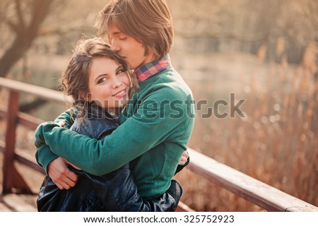 happy young loving couple hugs on the walk on wooden bridge with autumn field on background - stock photo