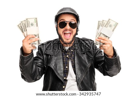 Happy young male biker holding few stacks of money and looking at the camera isolated on white background - stock photo