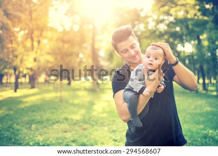 happy young male, father holding 3 months old infant and having a good time in park. Father and son concept at sunset  - stock photo