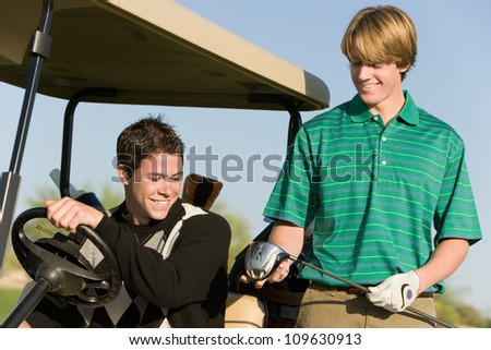 Happy young male friends looking at golf club - stock photo