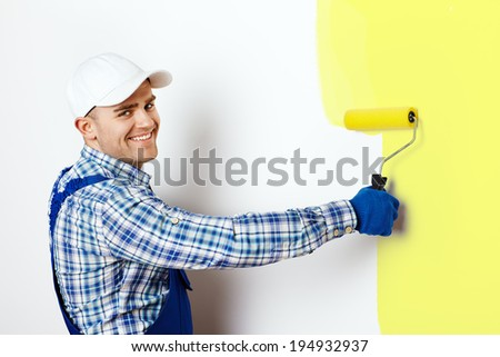 Happy young male painter painting a wall - stock photo