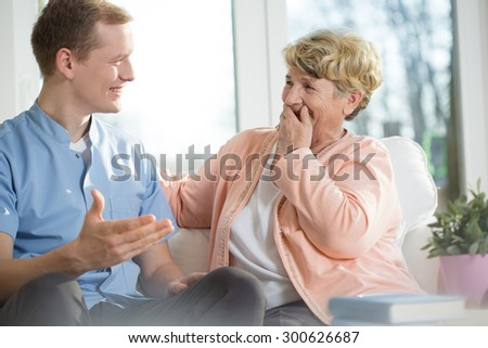 Happy young man and elderly woman are laughing - stock photo