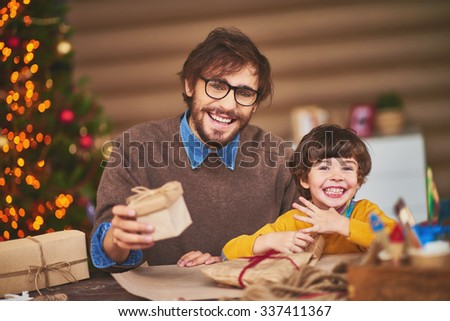Happy young man and little boy wrapping gifts - stock photo