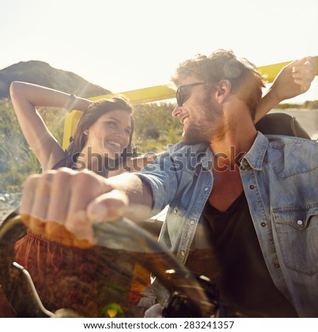 Happy young man and woman in a car enjoying a road trip on a summer day. Couple out on a drive in a open car. - stock photo