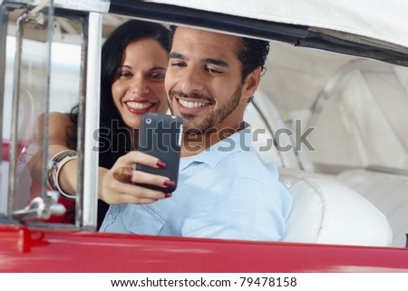 happy young man and woman smiling while taking snapshot with cell phone camera from red vintage convertible car - stock photo