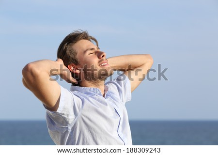 Happy young man breathing deep with hands in the head with the horizon in the background - stock photo