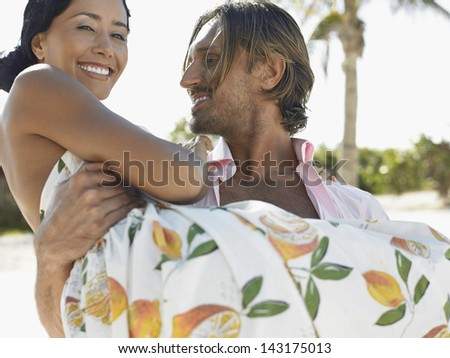 Happy young man carrying woman during their honeymoon on beach - stock photo