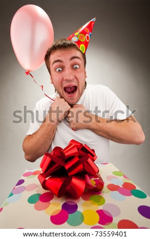 Happy young man celebrating birthday with gift and balloon - stock photo