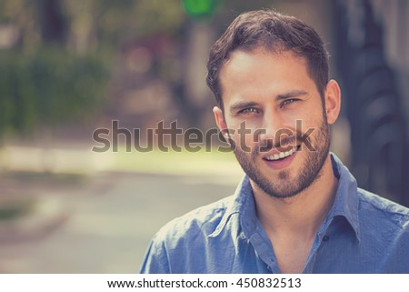 Happy young man. Closeup portrait of handsome guy in casual shirt smiling while standing against city urban background - stock photo