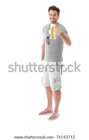 Happy young man drinking beer, holding beer mug, smiling.? - stock photo