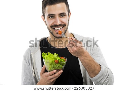 Happy young man eating a salad, isolated on white background - stock photo