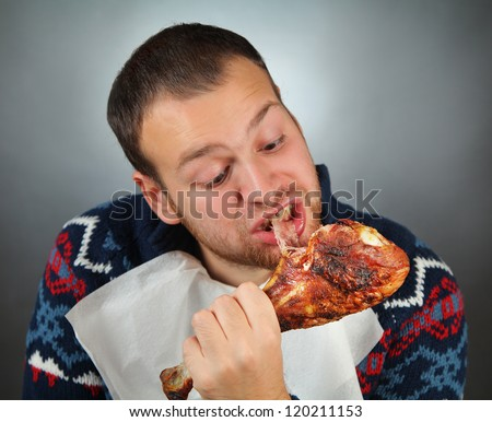 happy young man eating meat - stock photo