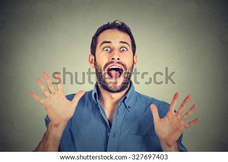 Happy young man going crazy screaming super excited isolated on gray wall background  - stock photo