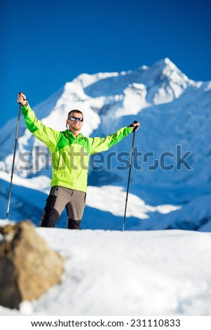 Happy young  man hiker exploring trekking in high Himalaya Mountains in Nepal. Hiking climbing in white winter or autumn beautiful nature on snow. Annapurna peak in background and clear blue sky - stock photo