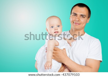 Happy young man holding a baby - stock photo