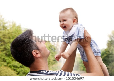 Happy young man holding a smiling 8 months old baby - stock photo
