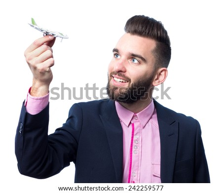 Happy young man holding a toy plane against white background - stock photo