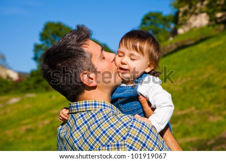 Happy young man holding and kissing a 16 months old child - stock photo