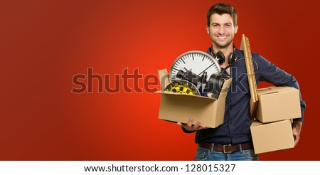 Happy Young Man Holding Cardboxes On Red Background - stock photo
