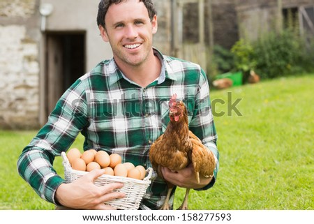 Happy young man holding his chicken and basket of eggs in his garden - stock photo