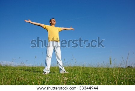 Happy young man in casual on the meadow, smile spreading his arms, summer sunny day - stock photo