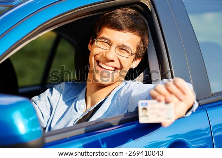 Happy young man in glasses showing his driving license from open car window - stock photo