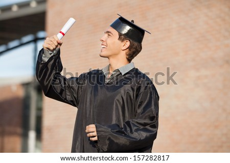 Happy young man in graduation gown looking at certificate on university campus - stock photo