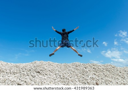 Happy young man in motion jumping happily against blue sky landscape. - stock photo