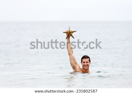 happy young man in ocean showing a starfish - stock photo
