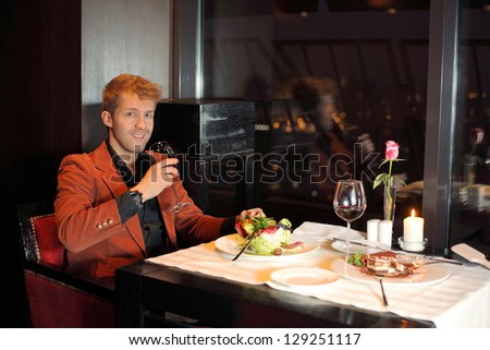 Happy young man in red suit in a restaurant - stock photo