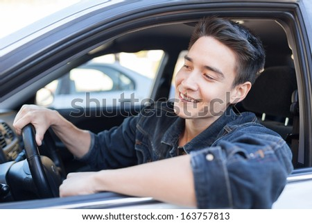 Happy young man in the car - stock photo