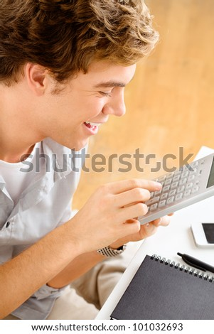 Happy young man is a student studying at home holding calculator - stock photo