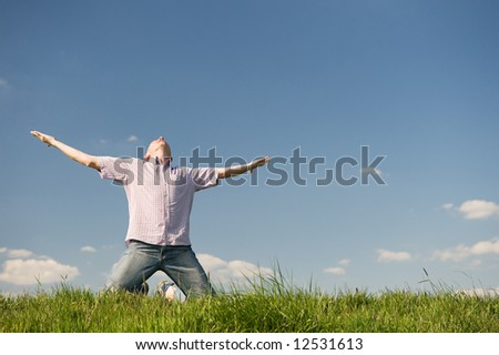 Happy young man is raising his arms into the sky - stock photo