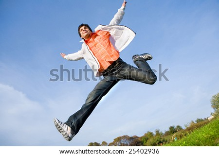 Happy young man - jumping  end fly in blue sky. - stock photo