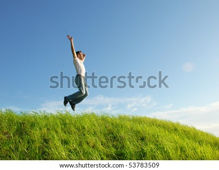 Happy young man jumping on the meadow - stock photo
