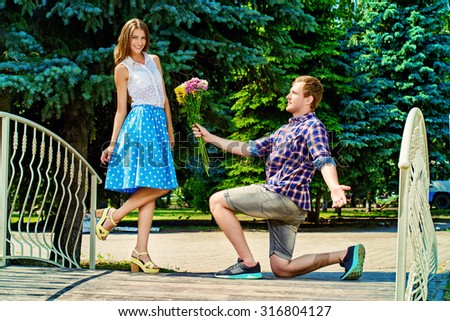 Happy young man makes a proposal to his girlfriend. Sunny summer day.  - stock photo