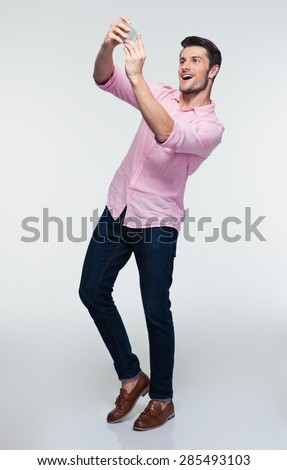 Happy young man making selfie photo on smartphone over gray background - stock photo