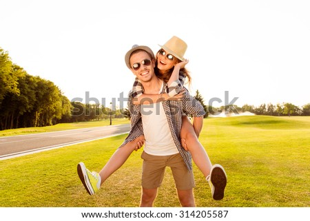 Happy young man piggybacking his girlfriend.  - stock photo